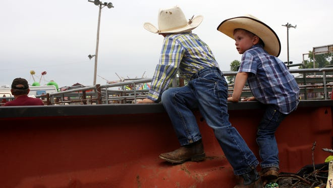 Jett Jahnke, 3, right, and cousin Tate Moore, 3, climb onto the side of a pickup truck during the Friday Night Main Event rodeo at the Johnson County Fair on Friday, July 25, 2014 in Iowa City, Iowa.
