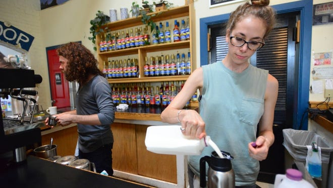 Speeder & Earl's employees Sarah Glick, right, and Matt White prepare coffee for customers Tuesday morning.