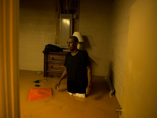 Willie Dunlap looks at his flooded basement from his