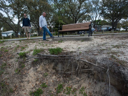 Navy Point residents, Kevin Wade, left, and Barry Hoppe, survey the erosion near the walking path in their neighborhood, Friday, April 6, 2018. Some Navy Point residents are concerned Escambia County's placement of artificial reefs in Bayou Grande, will not address the erosion issue and are a health hazard.