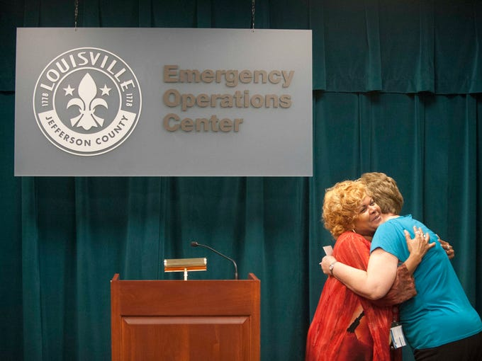 Jean Taylor, an information and referral specialist for MetroCall 311, hugs her boss, Marilyn Givan at an open house at its new facility inside the MetroSafe building on S. 4th Street. Taylor and Givan both have worked for the call agency for the past 25 years and were of its original seven employees. 05 June 2014