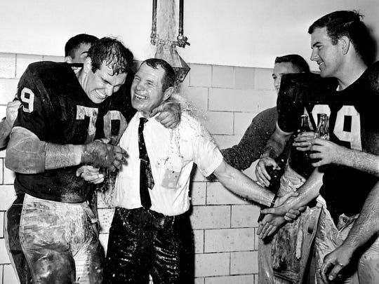 Vanderbilt head coach Jack Green, center, is held under