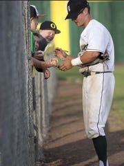 Tim Frith signs baseballs while playing for the Klamath Falls Gems this summer.