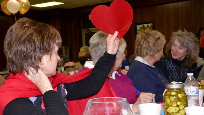 Donna Gundy bids on an auction item during the 16th annual Valentine's Dinner and Charity Auction.
