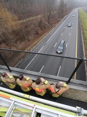 Hartsdale firefighters salute the funeral procession from the Secor Road overpass as the hearse returns to Westchester after the funeral Mass in New York.
