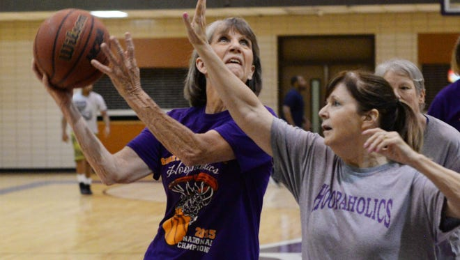 Judy Emberton (left) and Cay Evans practice for the Hoopaholics basketball team made up of women in their 50's and 60s.