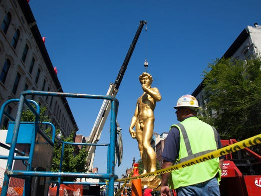 Adkins Export Packing and Machinery Mover employees lift the 30-foot-tall gold replica of Michelangelo's statue of David by Turkish conceptual artist Serkan Ozkaya in to it's final resting place outside of the 21C Museum Hotel May 2, 2012. The moving contractor transported the statue from Manhattan to Louisville.