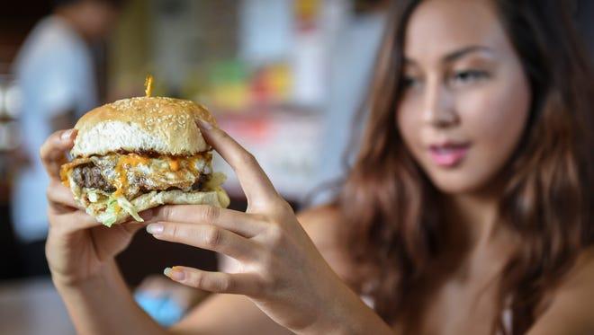 Gabi Mantanona, 18, sizes up a Denanche Burger at Meskla Dos on July 17.