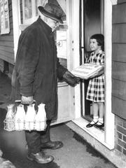 In this 1962 photo, a milkman receives a surprise birthday cake during a stop.