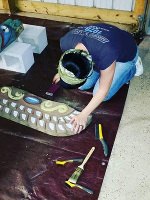 Kate Hart Nardone works on the restoration of a totem that once stood at Wheaton Arts and Cultural Center in Millville.