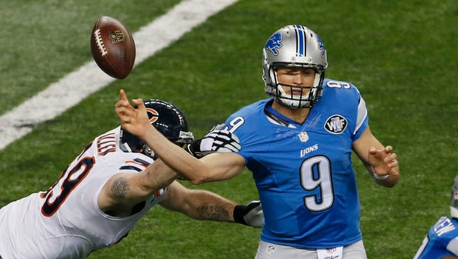 Chicago Bears defensive end Jared Allen (69) knocks the ball away from Detroit Lions quarterback Matthew Stafford (9) during the first half their Thanksgiving Day game in Detroit.