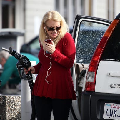 A customer prepares to pump gasoline into her vehicle