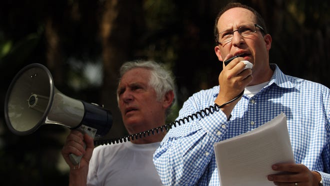 """""""We must stand with Israel,"""" urges Rabbi Adam Miller to fellow supporters at an Israel solidarity rally Sunday at Naples Pier. At left is Jerry Sobel."""