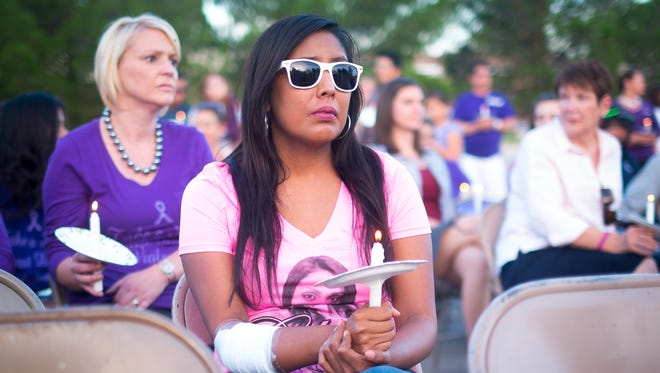 Lorena Kasero listens to speakers during a vigil to honor victims of domestic violence at the La Casa safe housing and counseling center on Thursday. Kasero was a friend of Graciela Hernandez, who died of blunt head trauma and multiple stab wounds in January. Hernandez's boyfriend, Corey Franklin, is charged with first-degree murder in the case.