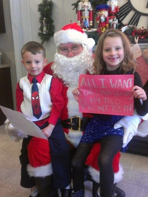 Seamus and Lydia Toshner of Eden sit on Santa's lap at the JG Custom Cabinetry open house in 2013.