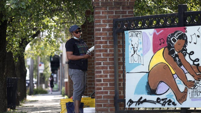 April Sunami paints a mural Wednesday along Mount Vernon Avenue on the Near East Side. The Maroon Arts Group was preparing the area nearby for a Juneteenth Celebration Saturday.
