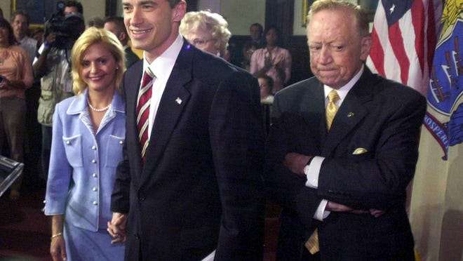 "FILE  In this Thursday, Aug. 12, 2004 file photograph, New Jersey Gov. James. E. McGreevey, middle, leaves with his wife, Dina Matos McGreevey, left, and his father, Jack McGreevey, following a news conference where he announced his resignation, in Trenton, N.J. Ten years after he announced that he was a ""gay American"" and would resign from office after a scandal-plagued stint as New Jersey governor, Jim McGreevey is back in government, this time mostly as an evangelist for prison reform. McGreevey, now 57, runs transitional programs for those getting out of prison and returning to Jersey City, where the mayor sees him as a policy and political adviser.(AP Photo/Daniel Hulshizer,file)"