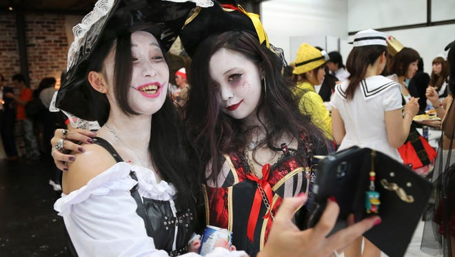 Aya Shiozaki, left, and Shoko Ushimaru pose for a photo during a Halloween party event in Tokyo.