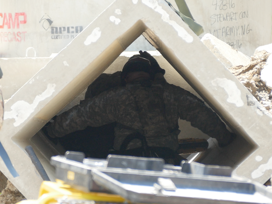 National Guard troops tunnel through a section of a collapsed building with power saws.