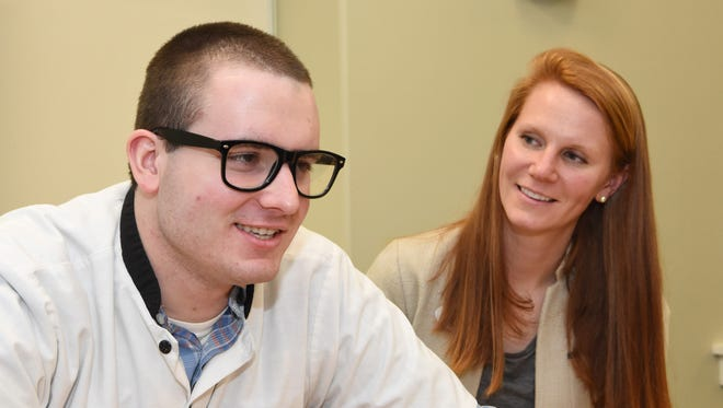 Michael R., left, a resident at the Anderson Center for Autism, sits with Inga McKay, right, a transition coordinator.