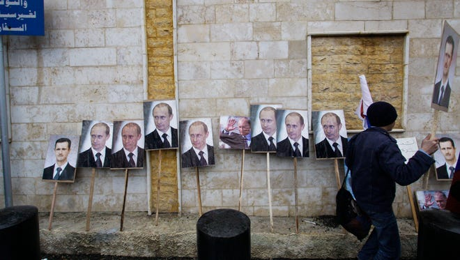 In this Sunday, March 4, 2013 file photo, photos of Syrian President Bashar Assad and Russian President Vladimir Putin are propped against a wall during a pro-Syrian government protest in front of the Russian Embassy in Damascus, Syria.