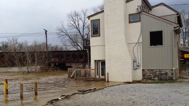 A fast-rising Little Miami River flowed into the rear paddle shack of the Loveland Canoe & Kayak on Karl Brown Way in Loveland Tuesday, April 3