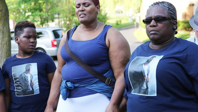 Christopher Davis' mother, Doretha Lock, prays with his brother Rashi Davis (left) and his grandmother Marilyn Lock during a gathering in May.