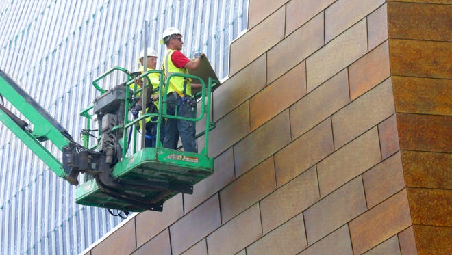 """Workers install zinc panels on the northwest side of the Milwaukee Bucks' new arena. The panels will provide the signature color and feel to the massive$524 million facility that is to open in time for the 2018-'19 NBA season. Those panelsstirred some of the most passionate debateover the design of the arena, with some detractors saying they would give the arena a """"Rust Belt"""" feel. Project designers, however, said the zinc panels can take on the look of wood or leather and will change appearance in varying degrees of light."""