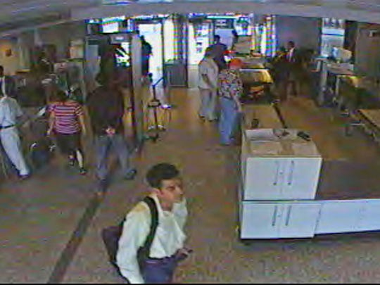 Khalid al-Mihdhar, wearing the yellow shirt in the foreground, passes through the security checkpoint at Dulles International Airport in Chantilly, Va., on Sept. 11, 2001.