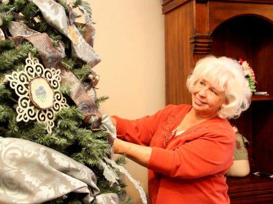 Ingret Van Dyk decorates one of the trees in the home of Cheri Panzer which will be featured in the 2015 Home Tour.