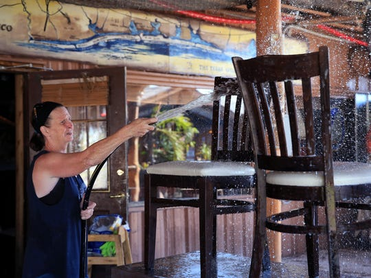 Lynn Mitchell, an employee of Moby Dick's in Port Aransas, TX, washes restaurant chairs on Tuesday, September 12, 2017. Employees and the owners have been cleaning up from Hurricane Harvey since it happened.