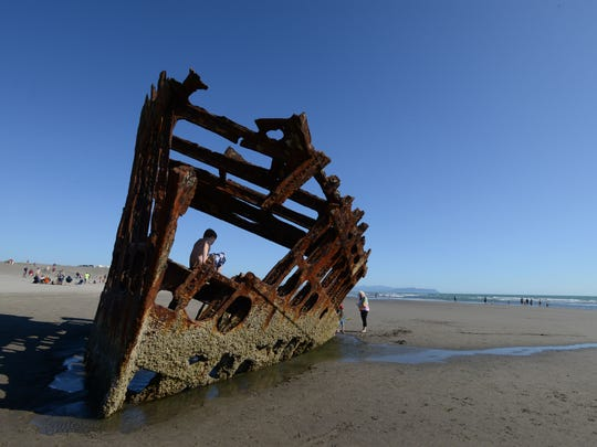 Children explore the rusty remains of the century-old shipwreck Peter Iredale along the beach at Fort Stevens State Park near Astoria on July 26. on Saturday, July 26, 2014.