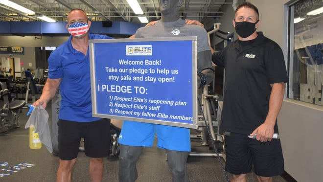 Elite Health & Fitness co-directors and co-owners Peter Rappoli (left) and Keith Callahan get a little help from a friend in explaining the new pandemic rules to customers.