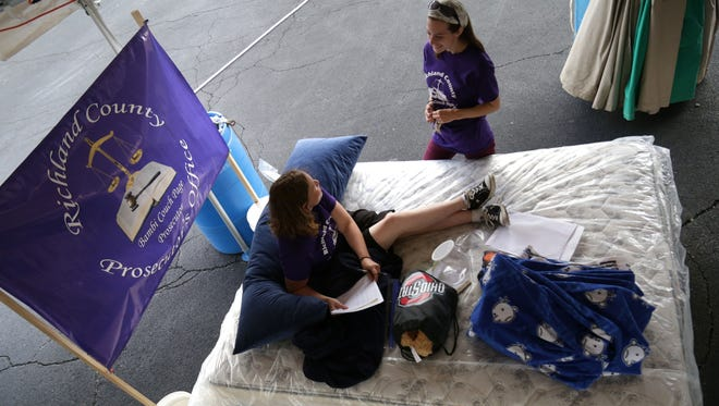 Amy Inzina, of the Richland County Prosecutor's Office, lays on a mattress while talking to Lillian Shun at the Great Sleep-Out Against Domestic Violence at Johnny's Mattress & Furniture Superstore on Thursday.