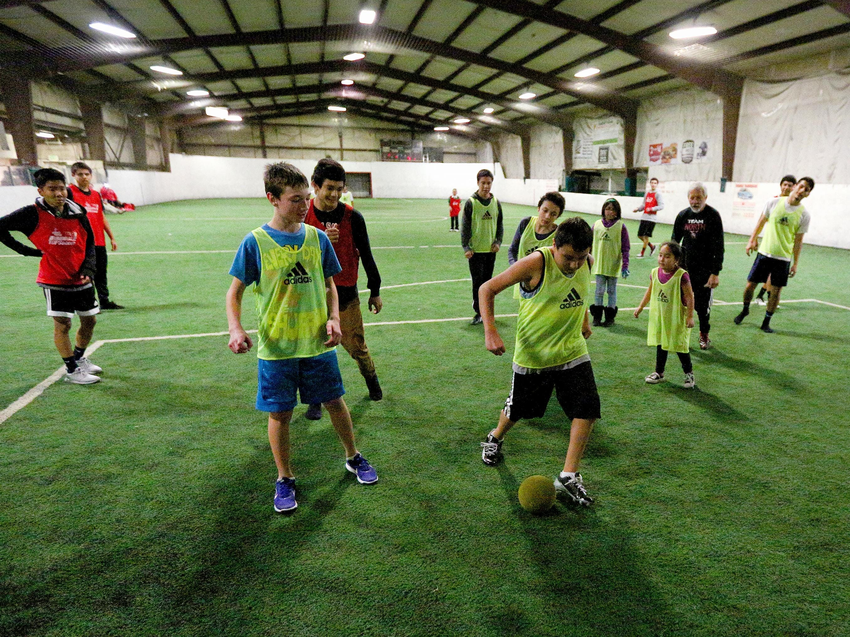 Chris Racine, 13, brings the ball into the box to score a goal during a youth soccer program with North Salem High School's boys soccer team, Wednesday, November 18, 2015, at Salem Indoor Soccer Center in Salem, Ore.
