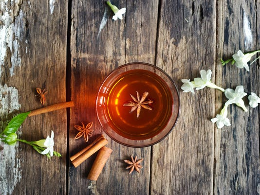 star anise in tea glass and cinnamon wooden background