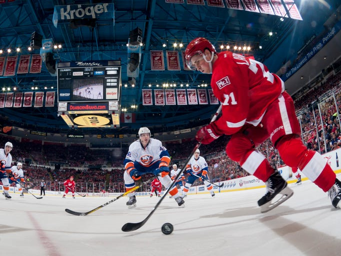 Detroit center Dylan Larkin keeps the puck away from