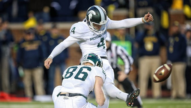 Oct 17, 2015; Ann Arbor, MI, USA; Michigan State Spartans place kicker Michael Geiger (4) kicks a extra point out of the hold of Michigan State Spartans wide receiver Matt Macksood (86) during the 1st quarter of a game at Michigan Stadium.