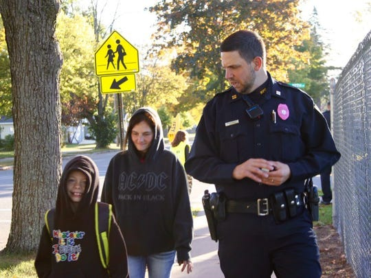 A police officer talks with students as they walk to