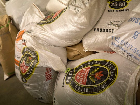 Bags of malted wheat sit in a warehouse of the Phoenix Brewing Company.