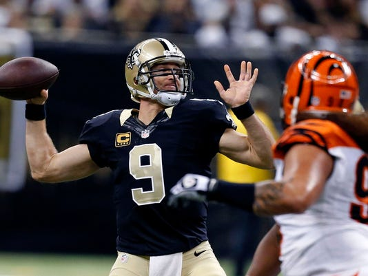New Orleans Saints quarterback Drew Brees (9) passes under pressure from Cincinnati Bengals defensive tackle Domata Peko (94) in the first half of an NFL football game in New Orleans, Sunday, Nov. 16, 2014. (AP Photo/Rogelio Solis)
