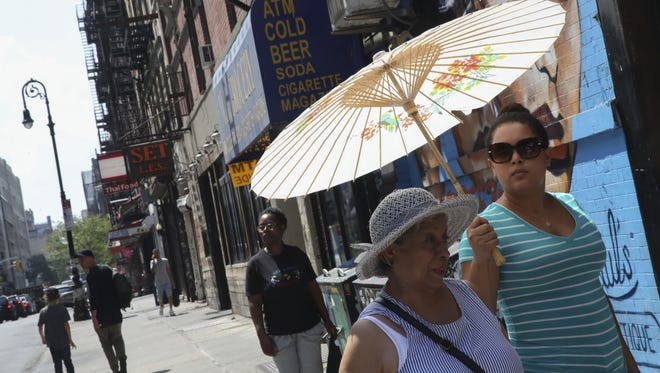 Women use a paper parasol to shield themselves from the sun, Wednesday, Aug. 29, 2018, in New York. The National Weather Service says temperatures in the 90s combined with high humidity are pushing the heat index past 100.