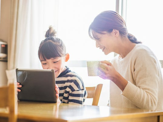Mother and daughter playing with a digital tablet in room