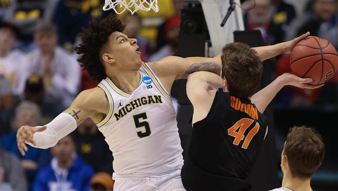 Michigan Wolverines forward D.J. Wilson blocks a shot by Oklahoma State forward Mitchell Solomon during the first half of U-M's 92-91 win Friday, March 17, 2017 at Bankers Life Fieldhouse in Indianapolis in the NCAA tournament.