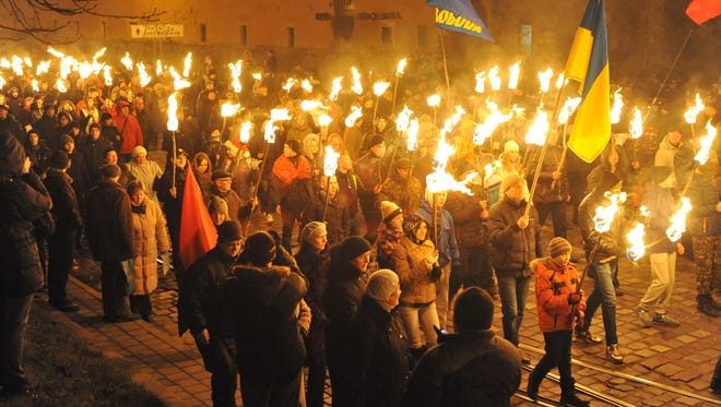 Nationalists hold torches during a march in the western Ukrainian city of Lviv on Jan. 1, 2014, as they mark the 105th anniversary of the birth of Stepan Bandera.