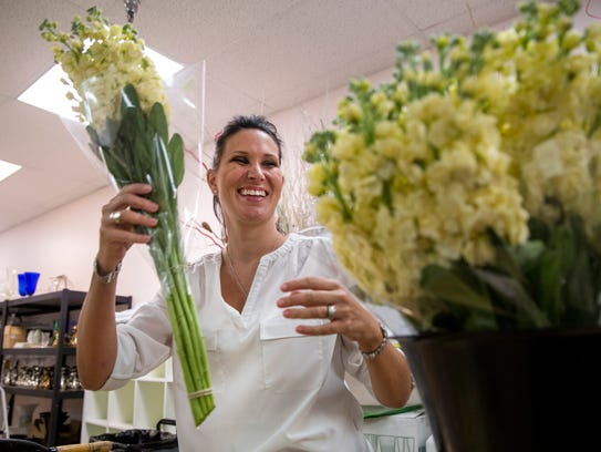Katie Huskin prepares bouquets of yellow stock at Flowers