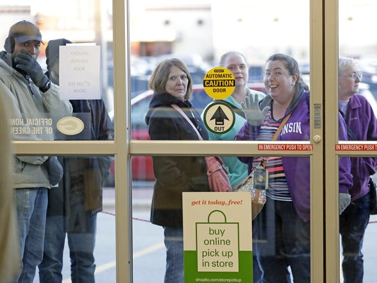 Holiday shoppers wait in line outside of Shopko at