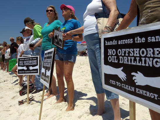 In this 2014 file photo, participants in the Hands Across the Sand gathering at Pensacola Beach Saturday afternoon line up on the shoreline to make their opposition to oil drilling in the Gulf of Mexico known. A smaller group gathered at the Gulfside Pavilion this year, but organizers said more people already at the beach joined the group on the shoreline.