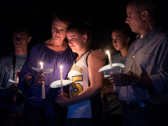 Mallory Grossman's mother, Dianne, hugs her daughter Carlee during a candlelight vigil in Rockaway Township. Mallory's father, Seth, is at right.