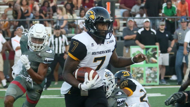 Southern Miss quarterback Kwadra Griggs avoids ULM players Saturday during their game in Monroe, La.